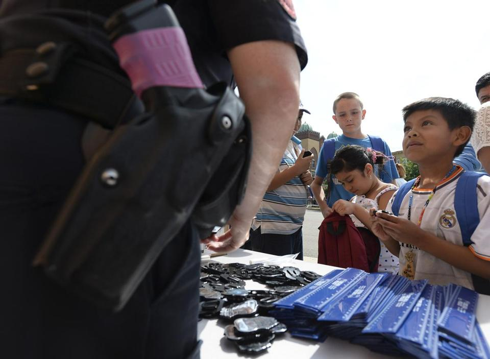 Jose Ramirez, 6, of Chelsea looked up at a police officer at the back-to-school celebration at Williams School.