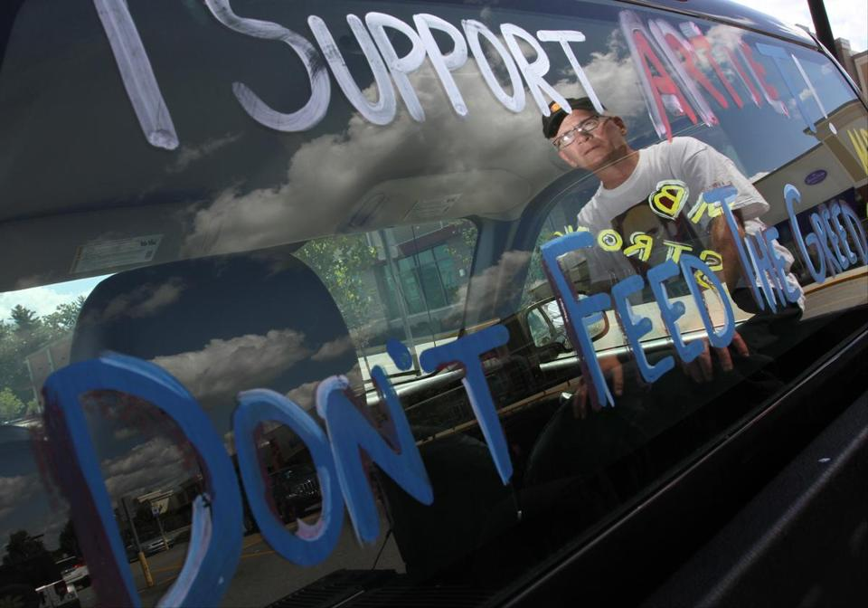 Paul Byron sits on the back of his pickup truck outside the Market Basket store in Epping, N.H.