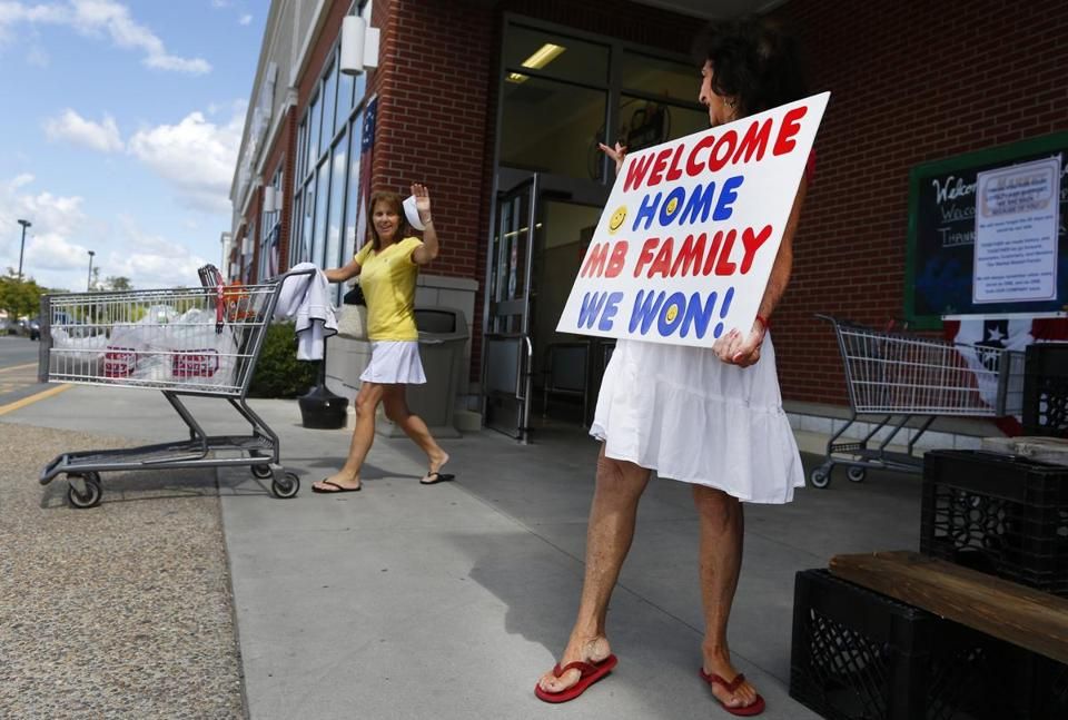 "Wilmington, Massachusetts -- 08/28/2014-- Loyal customer Elizabeth Cleary, of Billerica, (R) has been standing outside of the Market Basket in Wilmington, Massachusetts every day since the standoff started, her sign reads, ""Welcome Home MB Family. We Won!"" as she waves to a fellow customer August 28, 2014. Jessica Rinaldi/Globe Staff Topic: 29marketmain19 Reporter:"