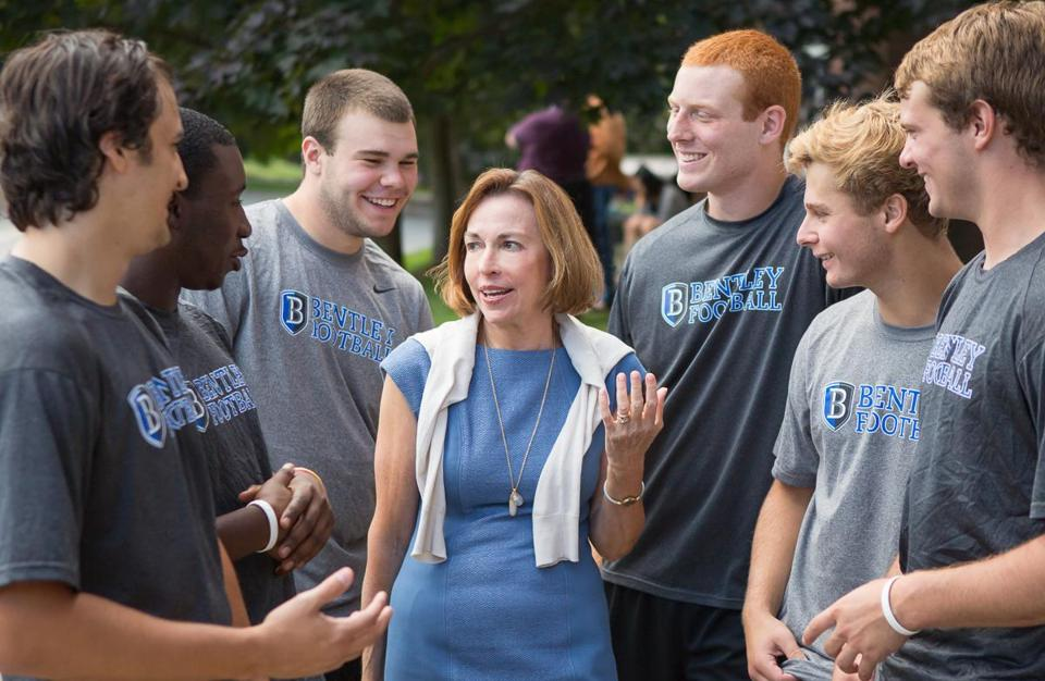 Gloria Larson, president of Bentley, with members of the university's football team.