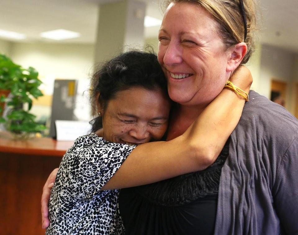 Fire survivor Doss Tha embraced Kristin Ross-Sitcawich, director of Community Teamwork Inc., which was instrumental in getting many of the victims back on their feet, on Tuesday.