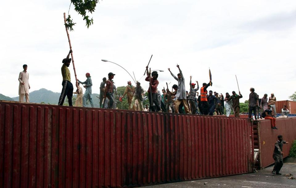 Supporters of cleric Tahir ul-Qadri and opposition politician Imran Khan commandeered containers Tuesday. Clashes between protesters and police have left three dead in three days.