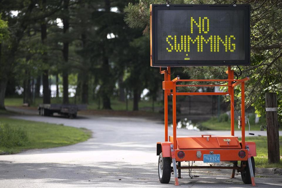 "Wellesley, MA - 6/3/2013 - An electronic sign flashed ""No Swimming"" and ""Beach Closed."" Morses Pond was photographed a day after 10-year-old Alexander Glennon, of Manchester, N.H. died, in Wellesley, MA on Monday, June 3, 2013. (Yoon S. Byun/Globe Staff) Slug: drowning Reporter: n/a LOID: 5.0.1725229525"