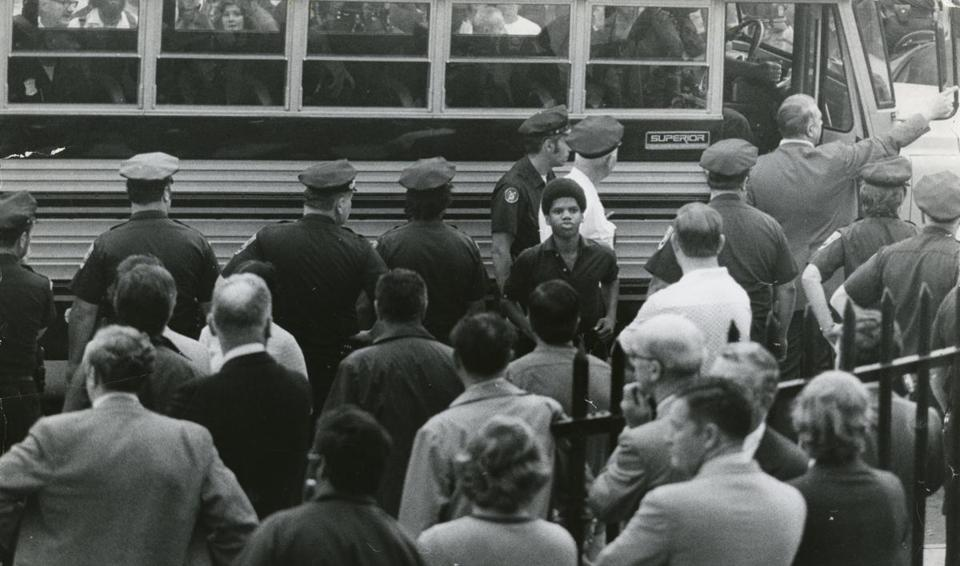 A black student was escorted off a bus by police officers outside South Boston High School.