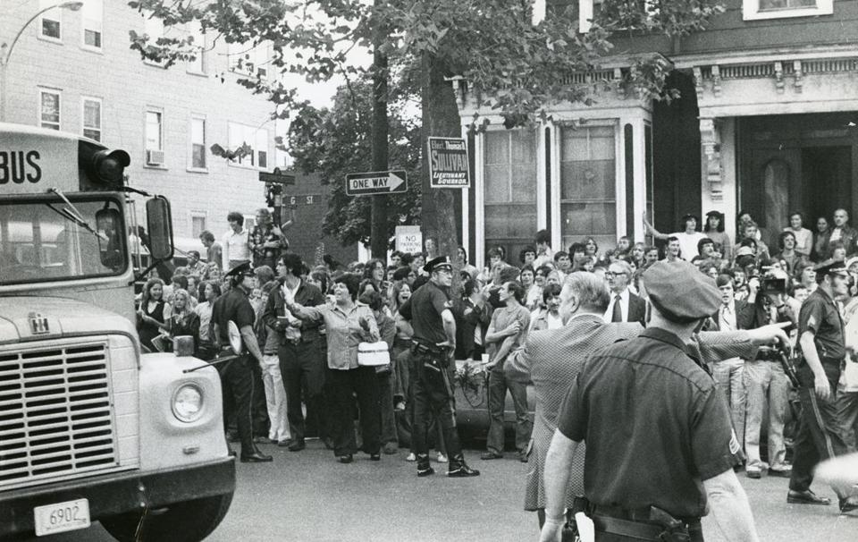 Boston, MA - 9/12/1974: Police hold back a crowd as a school bus drives by in South Boston on Sept. 12, 1974, the first day of school under the new busing system put in place to desegregate Boston Public Schools. The system was met with strong resistance from many residents of Boston s neighborhoods. (Dan Sheehan/Globe Staff) --- BGPA Reference: 140710_MJ_007