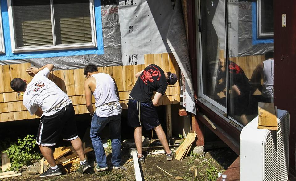 Members of Alpha Chi Alpha fraternity at Dartmouth College shingled a house for Habitat for Humanity.