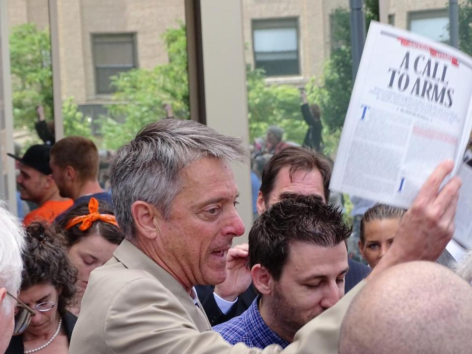 Bristol DA C. Samuel Sutter carried a Bill McKibben article on climate change outside the Fall River court on Monday.