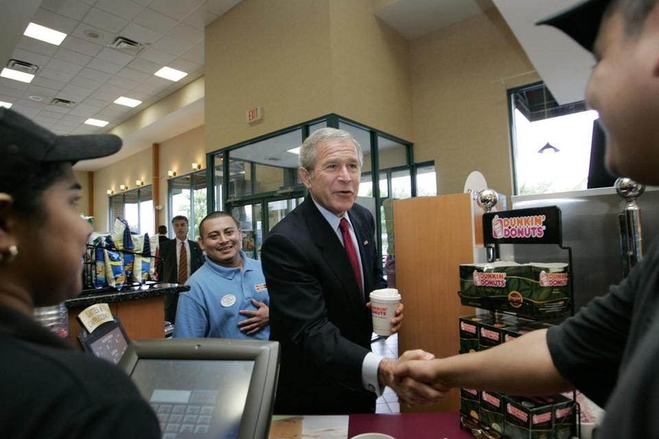 President Bush (center) stood with store manager Reynaldo Ramos as he greeted immigrant workers after buying coffee during an unscheduled stop at a Dunkin' Donuts in Alexandria, Va., on July 5, 2006.