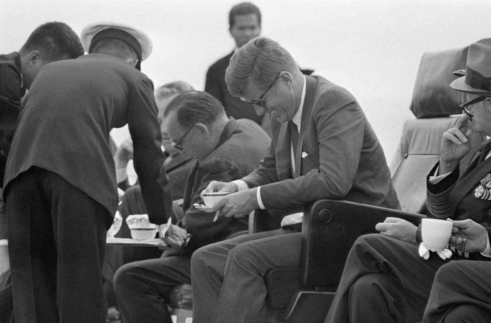 Gov. Edmund G. Brown let out a howl, to the amusement of President John F. Kennedy (right), after spilling a cup of coffee while watching special Navy maneuvers from the deck of the carrier Kitty Hawk.