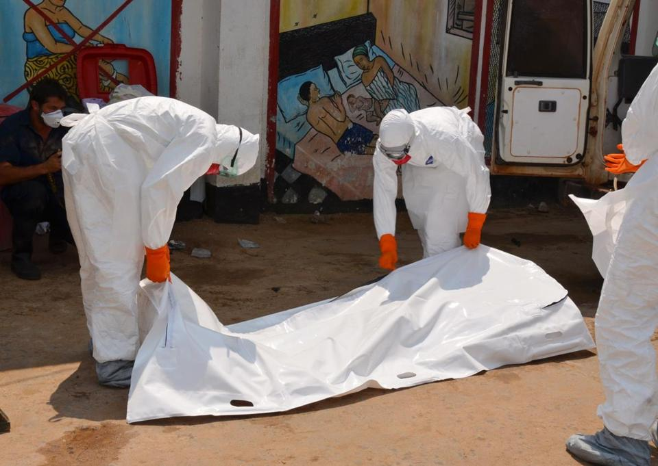 Health workers in protective suits carried the body of an Ebola victim in Liberia.