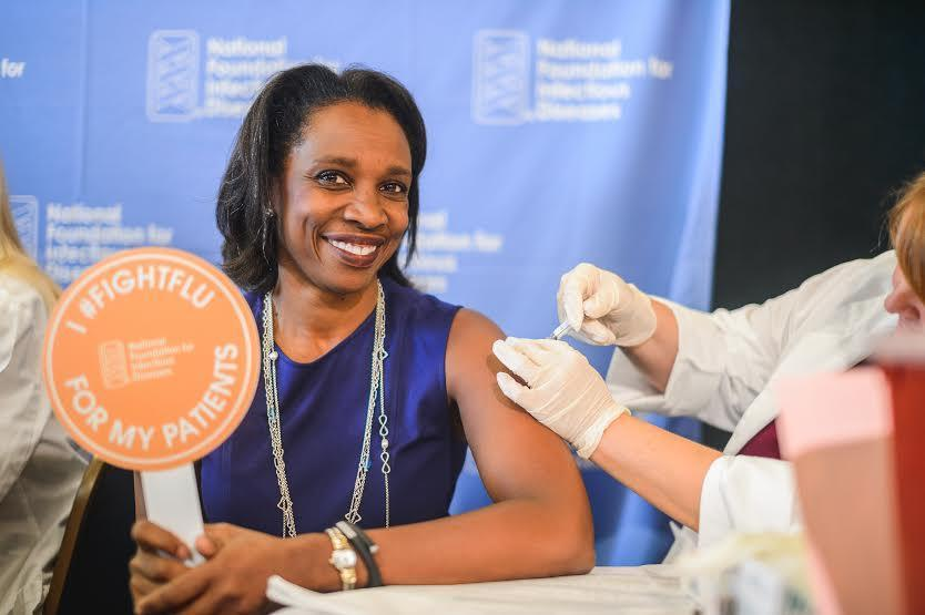 Dr. Laura Riley gets a flu shot at CDC briefing Thursday in Washington.