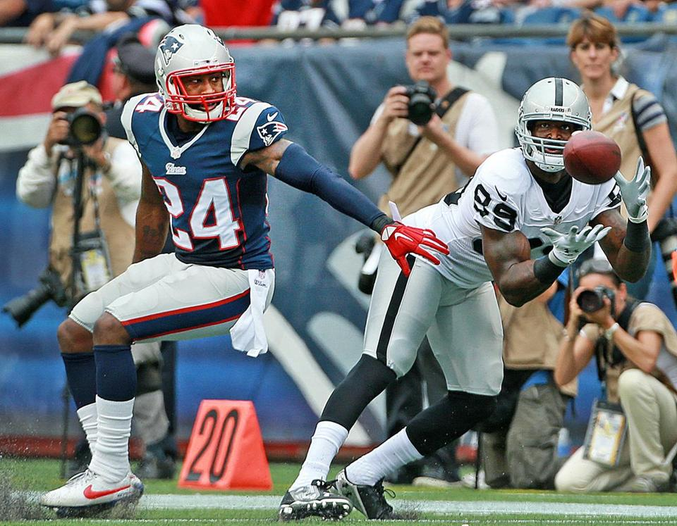 James Jones hauls in an 18-yard pass for an Oakland first down in front of Patriots cornerback Darrelle Revis. Jim Davis/Globe Staff