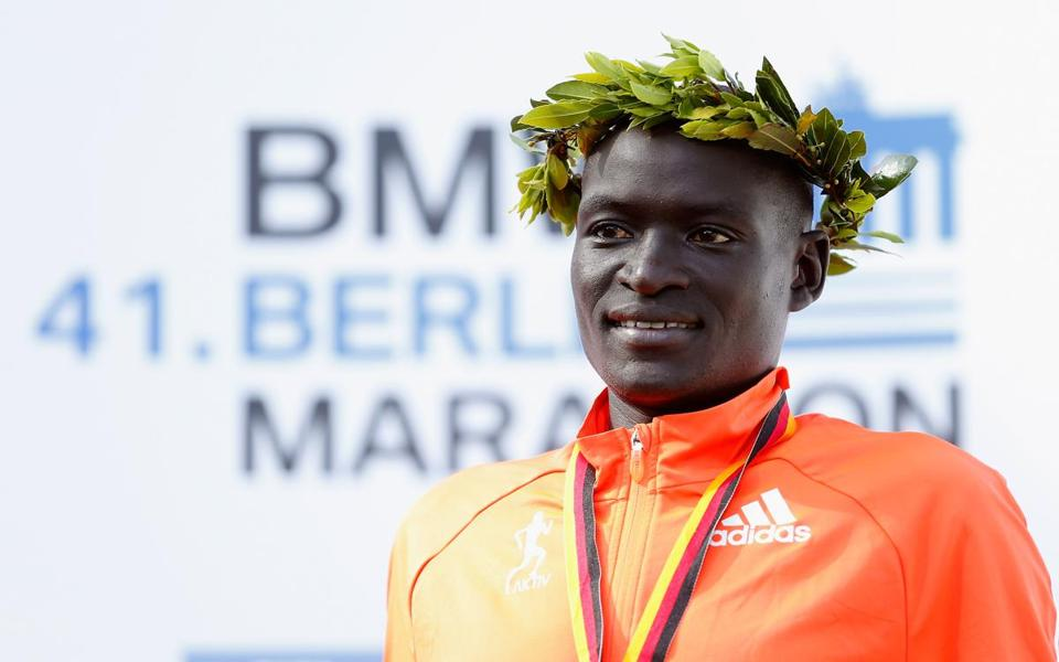 BERLIN, GERMANY - SEPTEMBER 28: First place winner and new world record holder Dennis Kimetto of Kenya poses on the podium after the 41th BMW Berlin Marathon on September 28, 2014 in Berlin, Germany. (Photo by Boris Streubel/Bongarts/Getty Images)