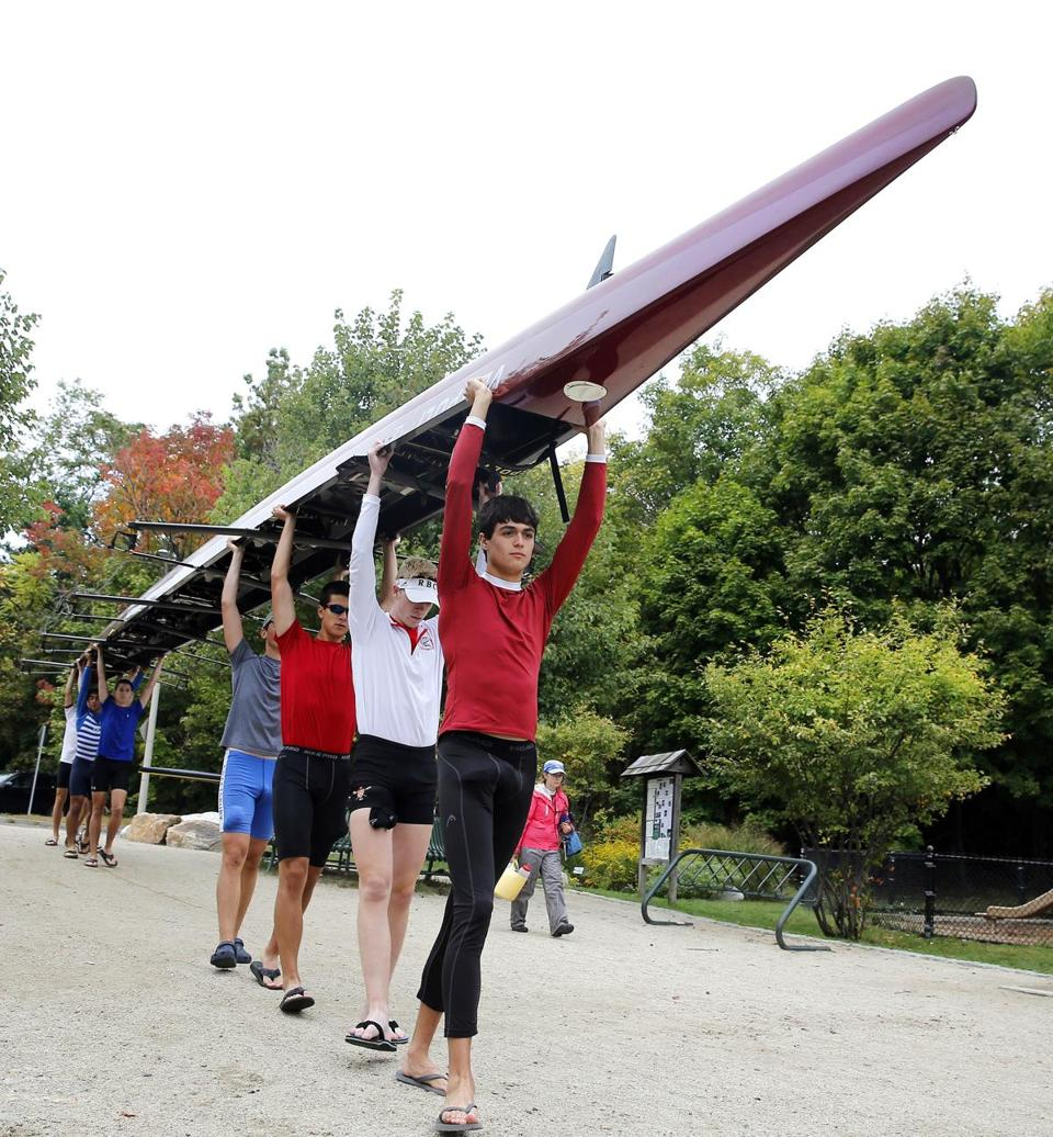 Arlington-Belmont crew member Adrian Tanner leads a boys eight team while they carry their boat to the water before practice in Arlington, Mass. Friday, Oct.3, 2014. (Winslow Townson for The Boston Globe)