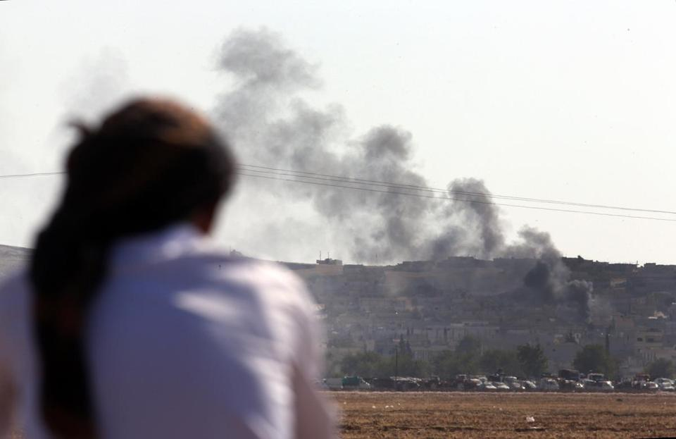 A Turkish Kurd sitting on the outskirts of Suruc, on the Turkey-Syria border, watched as smoke rose from a strike in Kobani.