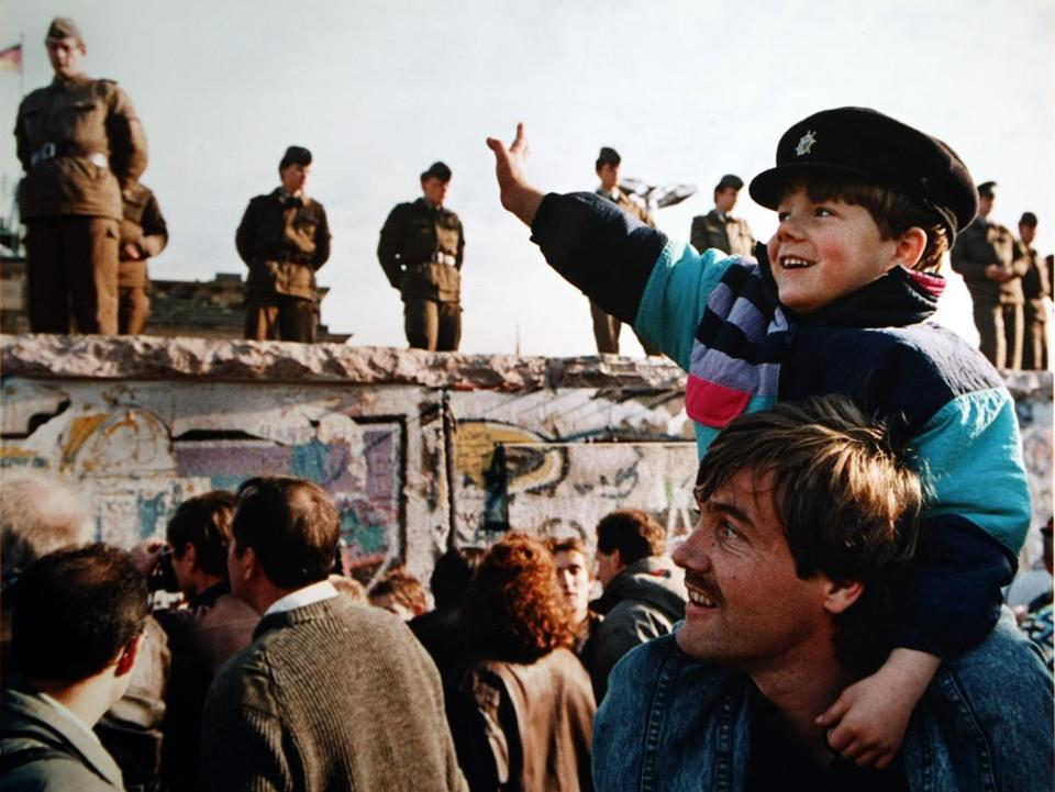 A boy waved to soldiers on the Berlin Wall in front of the Brandenburg Gate on Nov. 10, 1989, the day after the wall fell.