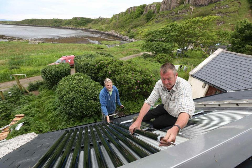 Residents fit solar thermal water heaters onto a cottage on the island of Eigg, Inner Hebrides, Scotland. Almost all of the energy on Eigg comes from renewable resources.