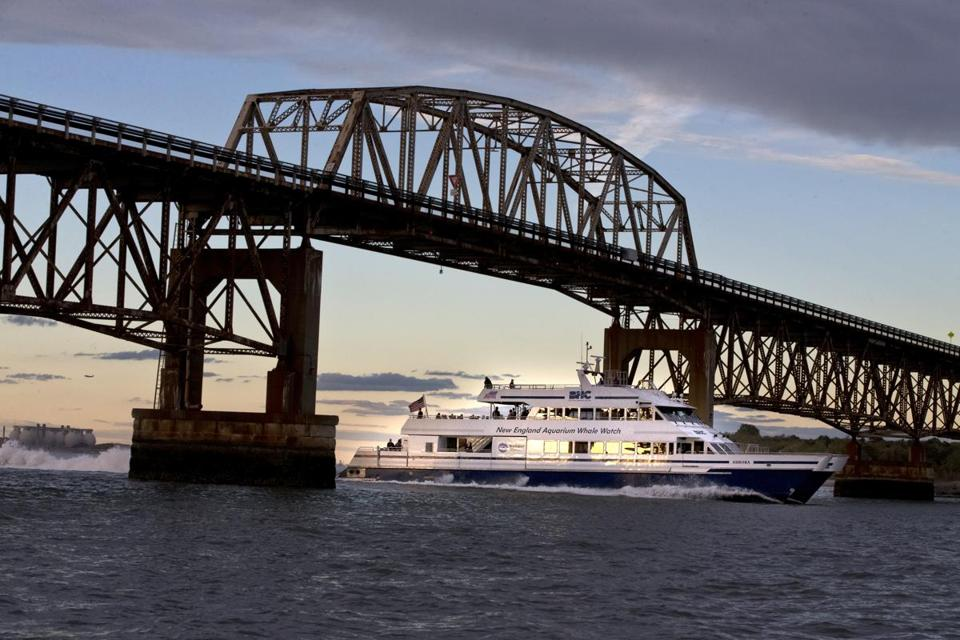 A New England Aquarium Whale Watch boat traveled under the Long Island Bridge.