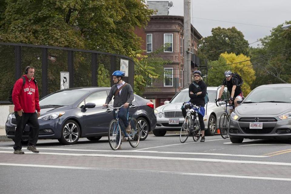 Bicyclists at the corner of Somerville Avenue and Beacon Street wait for the green light.