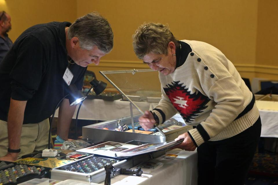 Nancy Zeloski (right) of Moultonborough, N.H., showed Robert Block of Connecticut photos of her marble collection.