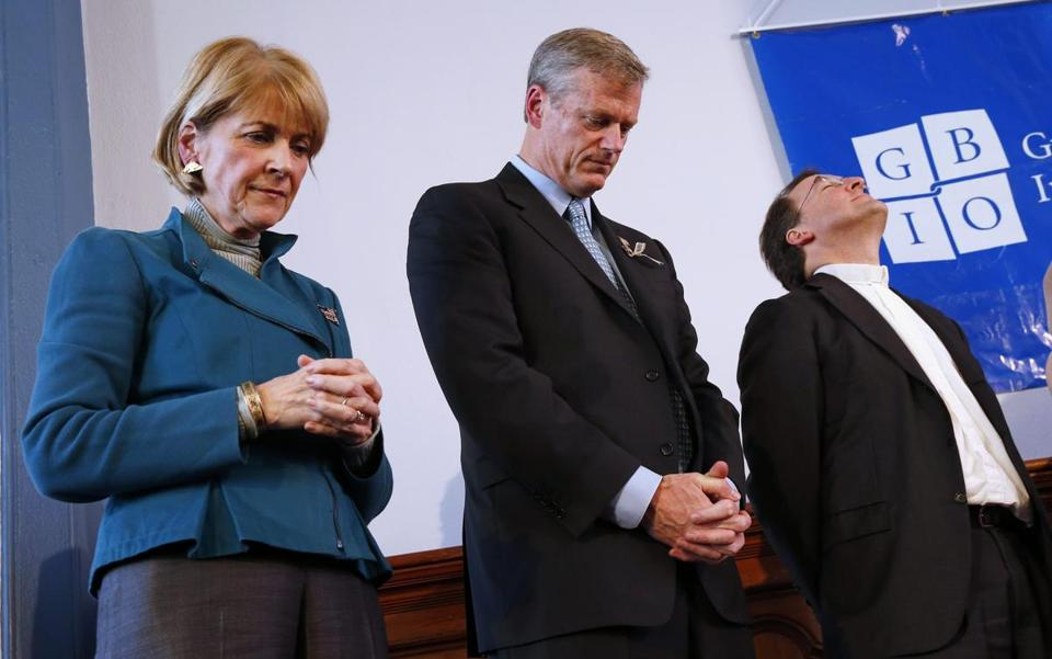 Martha Coakley and Charlie Baker bowed their heads in prayer next to Rev. Burns Stanfield at a Greater Boston Interfaith Organization Forum in Boston on Sunday.