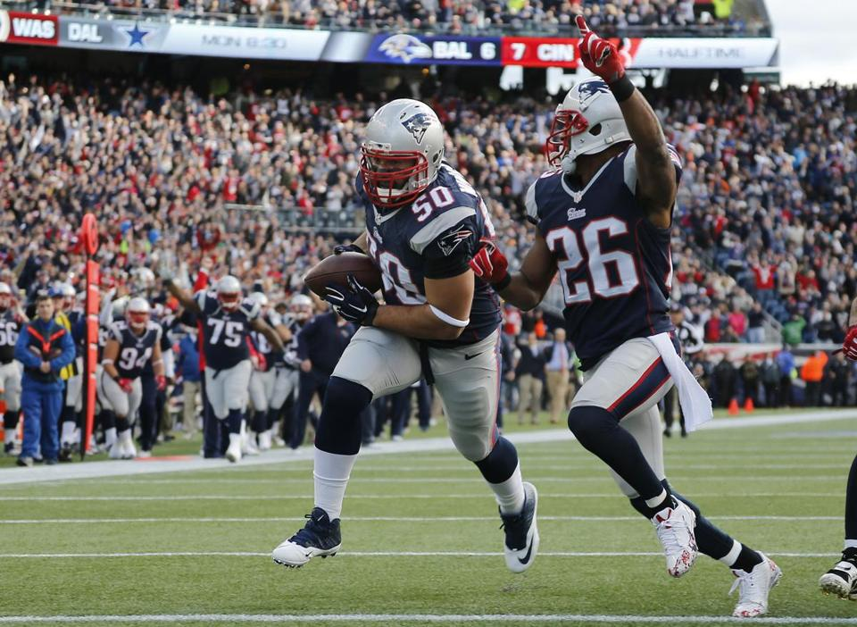 New England Patriots defensive end Rob Ninkovich (50) scores a touchdown cornerback Logan Ryan (26) after recovering a fumble by Chicago Bears quarterback Jay Cutler in the first half of an NFL football game on Sunday, Oct. 26, 2014, in Foxborough, Mass. (AP Photo/Elise Amendola)