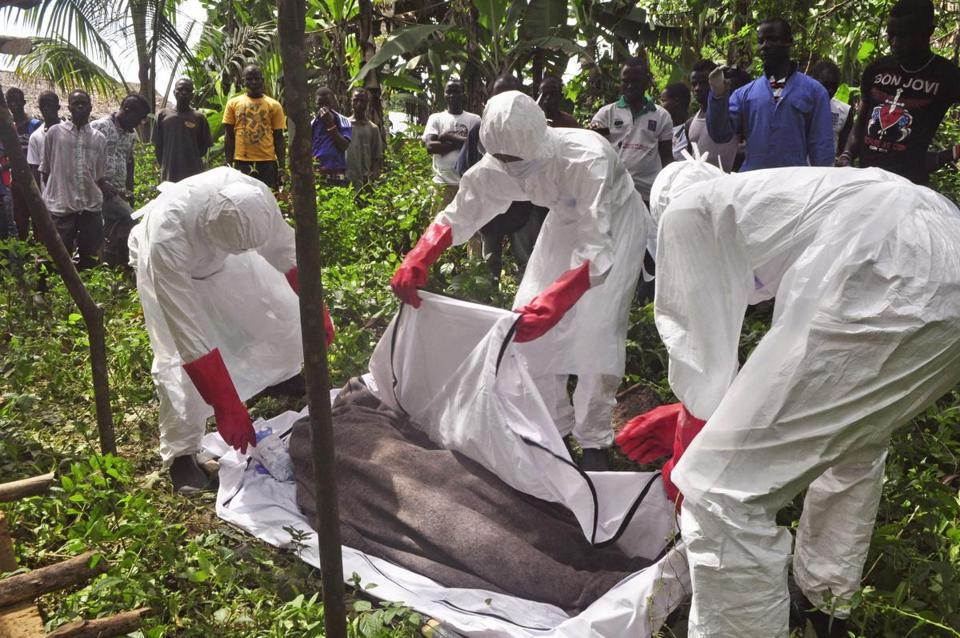 Health workers prepared the body of a man suspected of dying of  Ebola near Monrovia, Liberia, over the weekend.