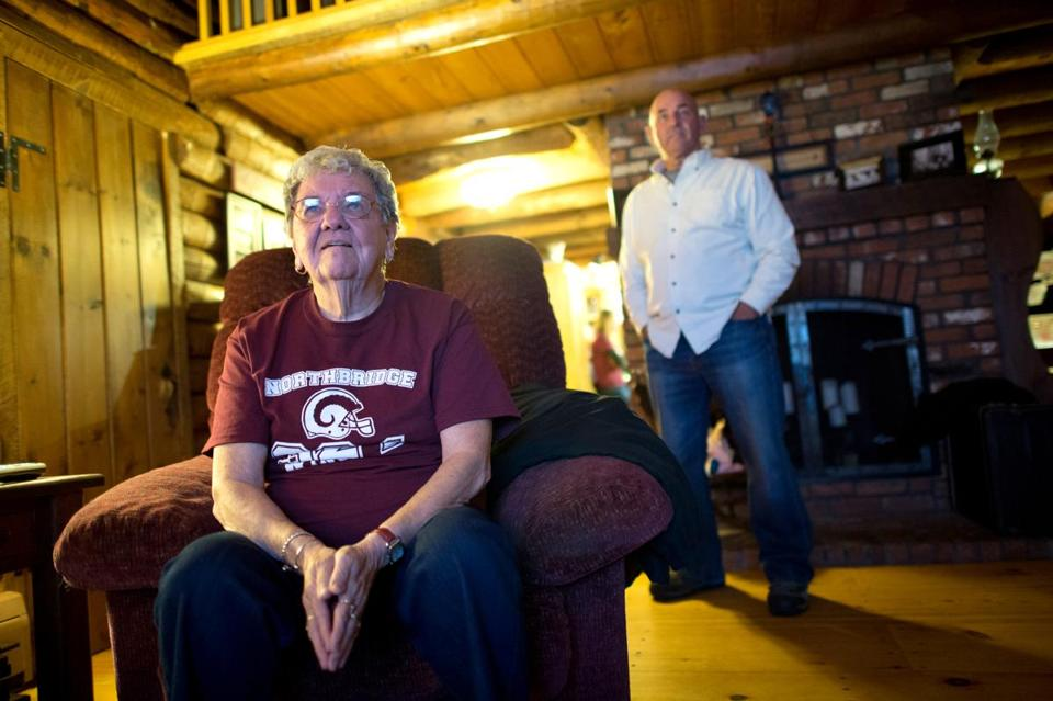 Alfreda LaChapelle watches the New England Patriots' game as Northbridge High School coach Ken LaChapelle, right, looks on at Ken's home in Uxbridge. Gretchen Ertl for The Boston Globe