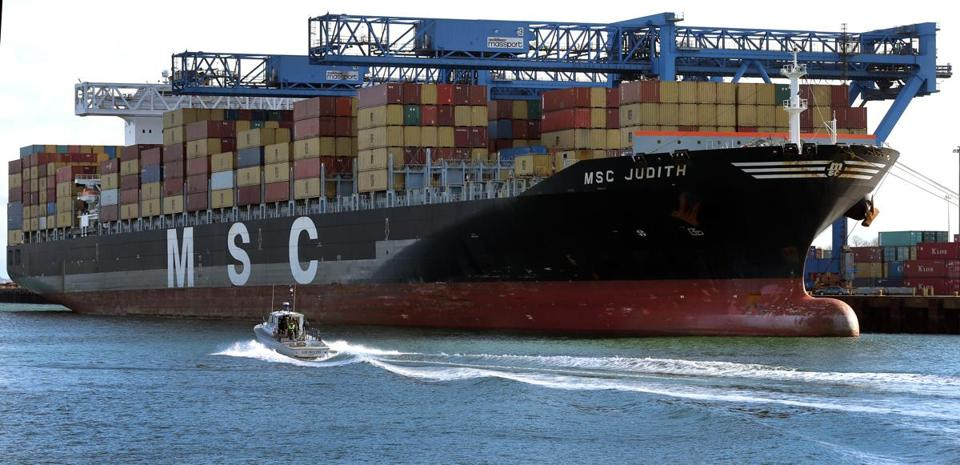 BOSTON, MA - 11/14/2014: Boston Police boat passes along the MSC JUDITH. The largest container ship to arrive at Boston Harbor, it was at Conley Terminal and weighs 89,954 gross tons and draws 12 meters being unloaded -(David L Ryan/Globe Staff Photo) SECTION: BUSINESS TOPIC 15ship(1)