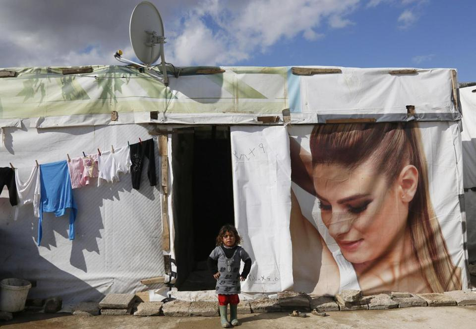 A Syrian refugee girl stood near a tent at a refugee camp.