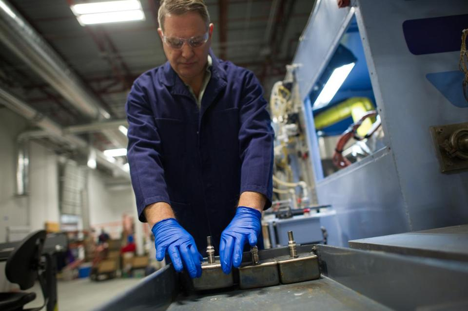 An Ambri process engineering technician, Henry Phillips, placed a battery cell alongside other cells in a power core.