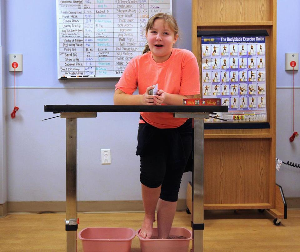 Emma Bowen, 10, of Taunton, who suffers from foot pain, soaks her feet in hot water at the Waltham center. (Wendy Maeda/Globe Staff)