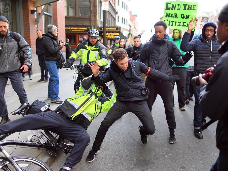 A Boston officer grabbed a protester who had knocked him off his bike on Tremont Street; the officer later let him go without charges.