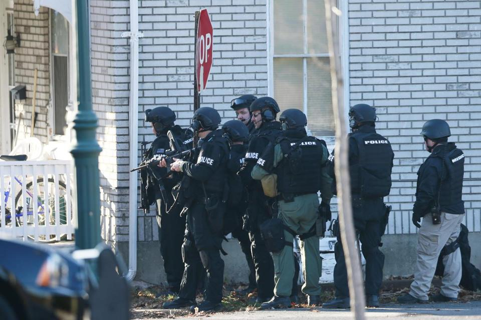 Police gather near a home in Souderton, Pa., where suspect Bradley William Stone is believed to have barricaded himself inside after shootings at multiple homes.