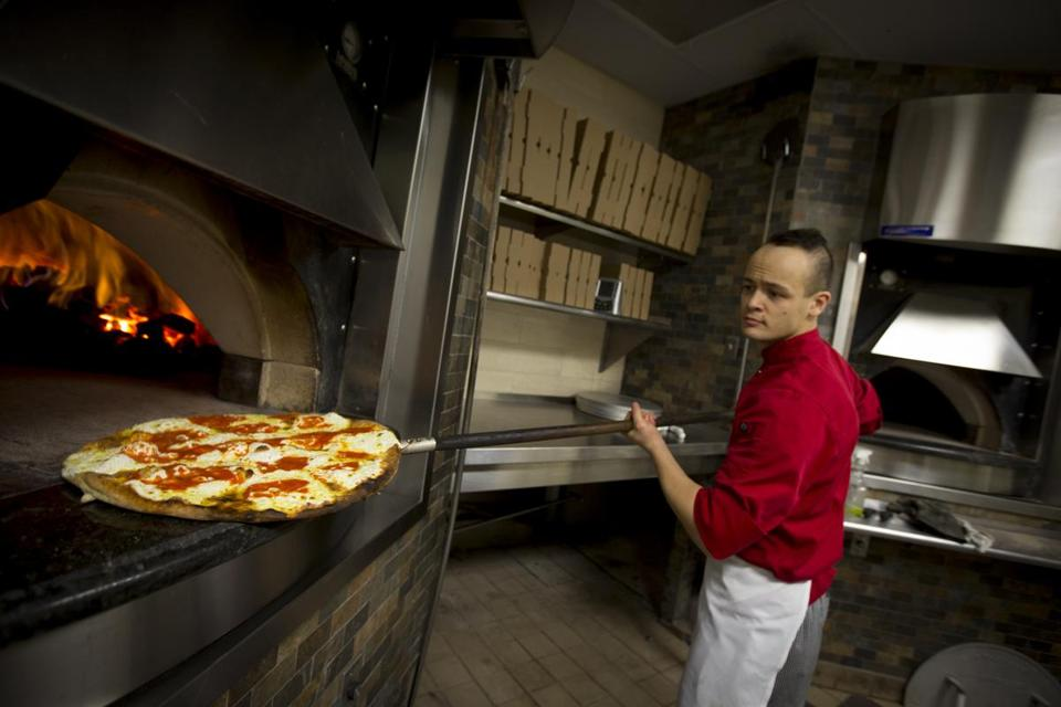 Executive chef Chris Howard uses a long-handled paddle to check on an order at Angelo's Coal Fired Pizza in Quincy.