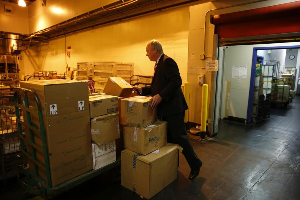 Mike Powers, manager of the greater Boston postal district, looked through packages to be sent as part of Operation Santa at the Post Office annex in South Boston.