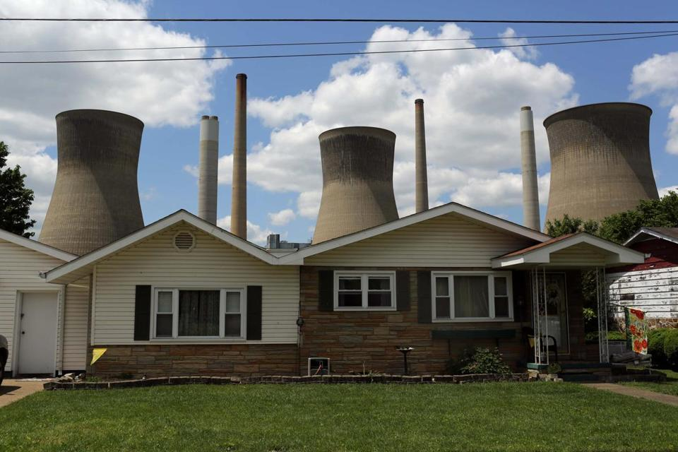 The John Amos coal-fired power plant is seen behind a modest home in Poca, West Virginia, in May.