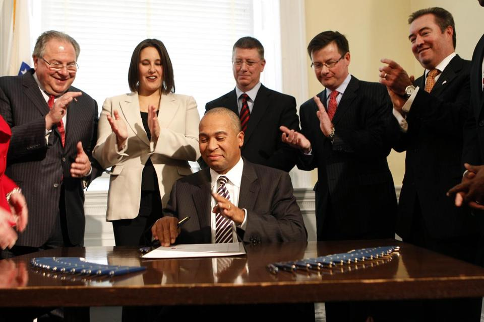 Lawmakers who helped craft the casino bill clapped after Governor Deval Patrick signed the legislation in November 2011.