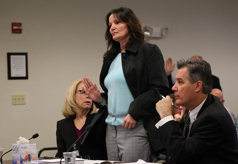 Nancy McGeoghean, flanked by her lawyers, Helen Holcomb (left) and John Cunha, took an oath at the start of the Dec. 29 hearing.