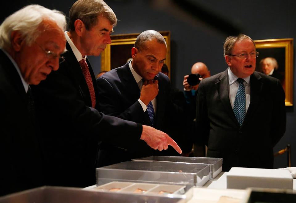 Secretary of State William Galvin, who is also chairman of the Massachusetts Historical Commission, second from left, pointed to an object as Governor Deval Patrick, center, looked on.