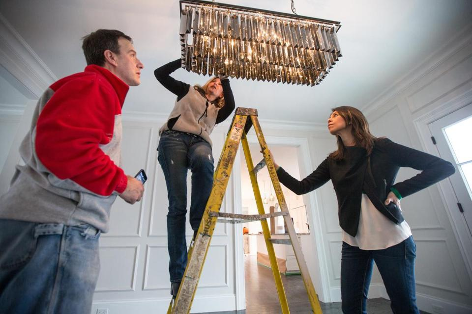 01/06/2015 NEWTON, MA L-R Project manager Glen Sargent (cq), contractor Cindy Stumpo (cq) and homeowner Alexandra Almonacid (cq) examine a dining room light fixture at the Almonacid family home.