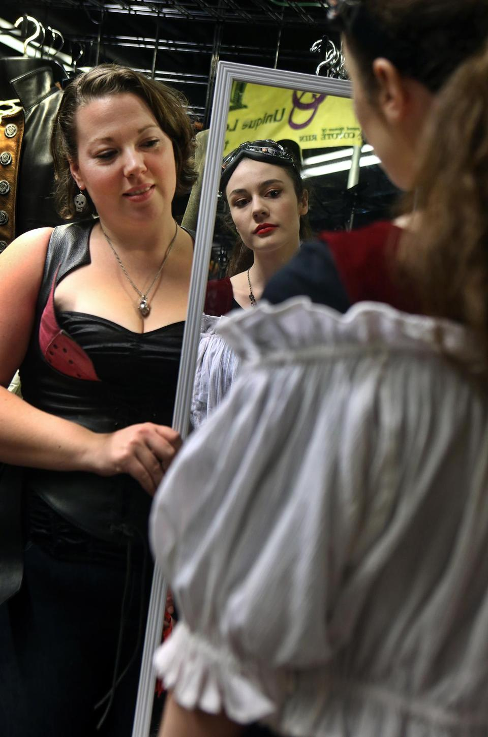 Boston, MA 1/18/15 Maia Schofield, 17, Hampstead, NH, right, comes to the Arisia science-fiction and fantasy convention for the costume-oriented activities. Here she tries on a blouse to go with a corset she bought the day before at the convention while Debbie Sarmir, who works for a vendor, holds the mirror.