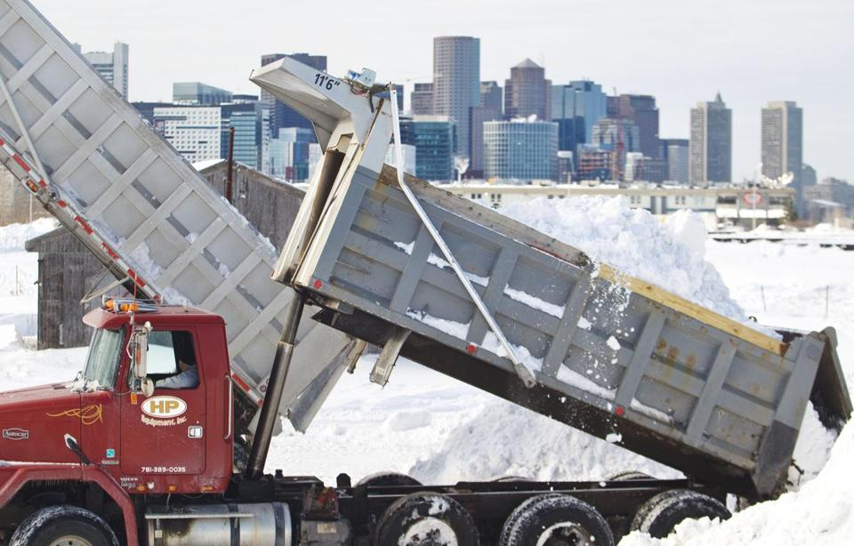 "1/28/2015 - Boston, MA - Dump trucks carrying snow that has been removed from Boston roadways and sidewalks dump their payloads in a lot on Tide Street in South Boston called a ""Snow Farm"" by Boston Mayor Marty Walsh, cq. Walsh explained that crews were removing large snow piles and dumping it in snow farms such as this one. Photo by Dina Rudick/Globe Staff."