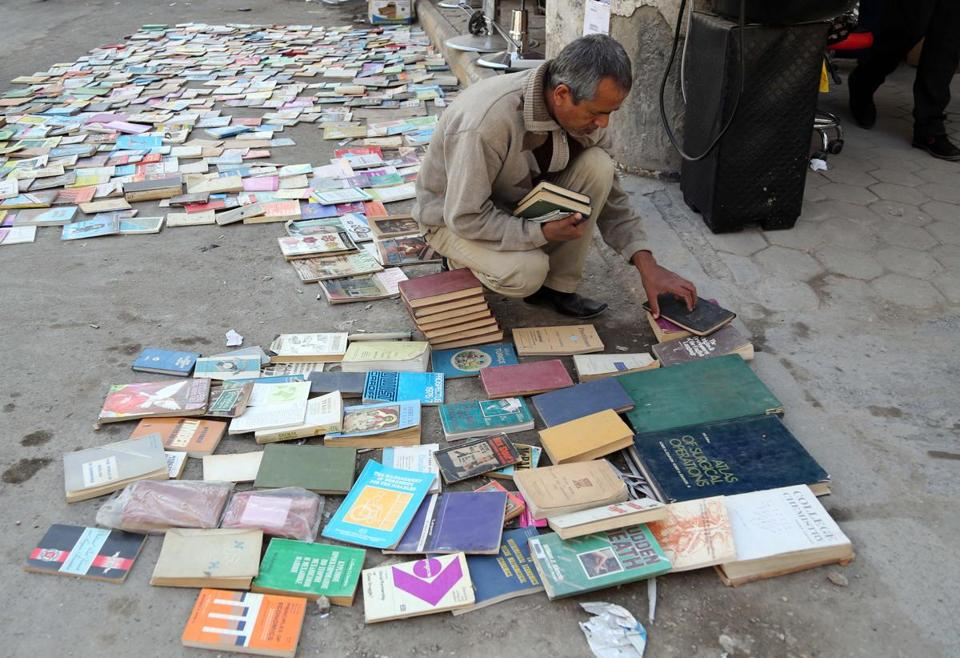 An Iraqi man visited a book market in Baghdad. But in the northern city of Mosul, Islamic State militants hit the Central Library, taking away 3,000 books and leaving behind only Islamic religious ones.
