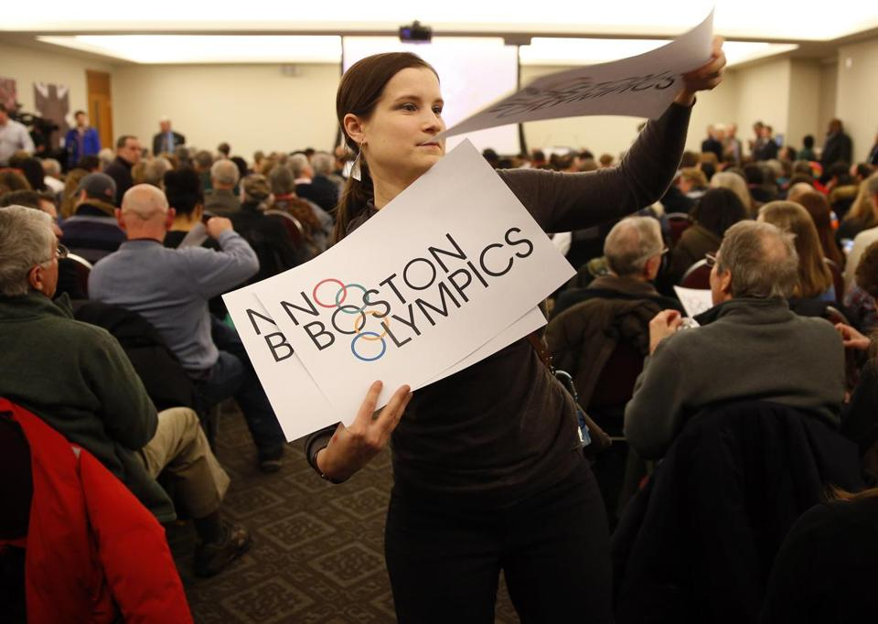 Claire Blechman, of Somerville, handed out No Boston Olympics signs before the start of an Olympic and Paralympic Bid Community Meeting.