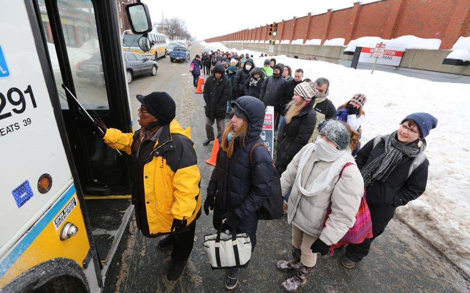 Commuters waited in a line that snaked from the parking lot through the Wollaston T station to board Red Line shuttle buses on Wednesday.