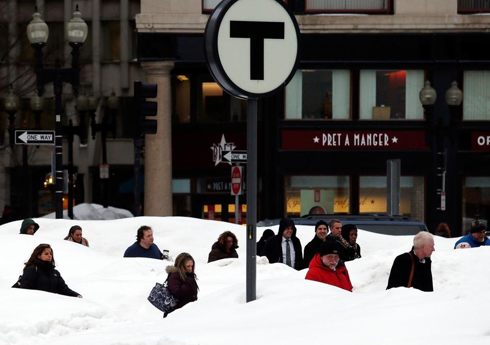 Mounds of snow surrounded commuters at an MBTA stop in downtown Boston on Thursday. Snow and rain are forecast over the weekend.