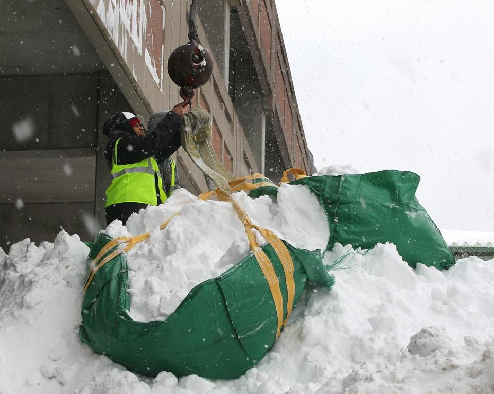 A crew removed snow by the bagful from a flat portion of the roof  at South Shore Plaza in Braintree early last month.