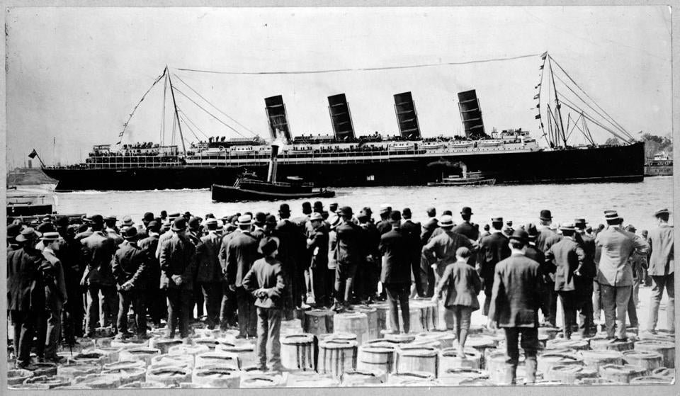 Title: RMS Lusitania, New York City, September 1907, stern-side view, during maiden voyage, with a large crowd of men, in foreground, standing on top of barrels. Date Created/Published: 1907. Medium: 1 photographic print. Library of Congress Prints and Photographs Division Washington, D.C. 20540 USA