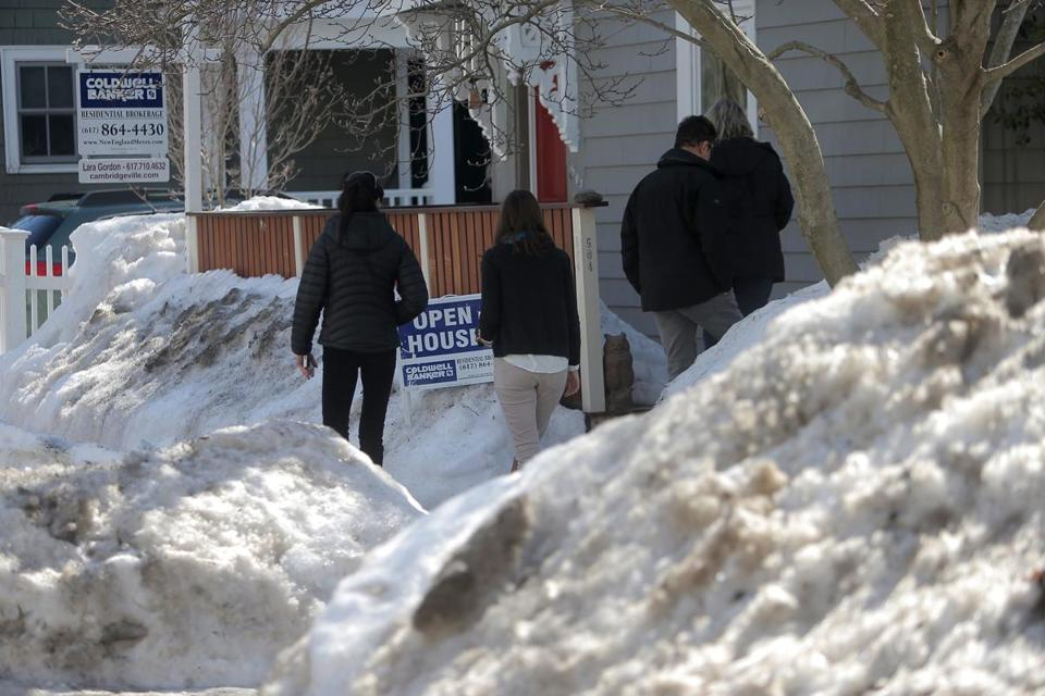 Cambridge, MA - 03/12/15 - Home shoppers enter an open house on Franklin Street. Lara Gordon is putting a home for sale and trying to deal with the mounds of snow in front of homes - including making sure that walkways are cleared. March usually kicks off the spring real-estate market, but right now houses are buried under heaps of snow, homeowners are dealing with ice-dam damage and agents can't even get for sale signs onto front yards. Realtors think this could be a really busy spring season as the economy has improved and buyers are trying to take advantage of the low interest rates. Except for that darn snow. Lane Turner/Globe Staff Section: BIZ Reporter: Deirdre Fernandes Slug: 12snowhomes